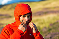 Trail runner adjusts hood of his red running windproof jacket.