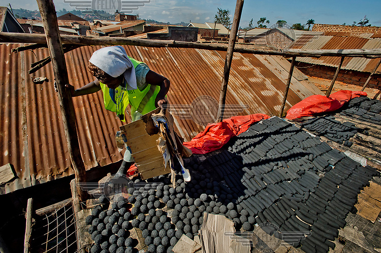 On the roof of the Lulana Communal Environmentalist's workshop, Prosse arranges different types of briquettes, made from recycled or waste cardboard and used for cooking fuel as an alternative to charcoal or wood, for drying.