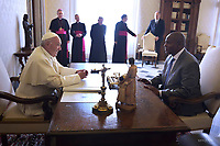 Pope Francis walks along with Central African Republic President Faustin-Archange Touadera during a private audience at the Vatican on January 25, 2018.