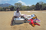 Young Man Washing Clothes On Chombe Beach