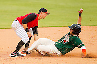 Kannapolis Intimidators shortstop David Herbek #12 puts the tag on James Wooster #22 of the Greensboro Grasshoppers as he tries to steal second base at CMC-Northeast Stadium on June 12, 2012 in Kannapolis, North Carolina.  The Intimidators defeated the Grasshoppers 2-1.  (Brian Westerholt/Four Seam Images)