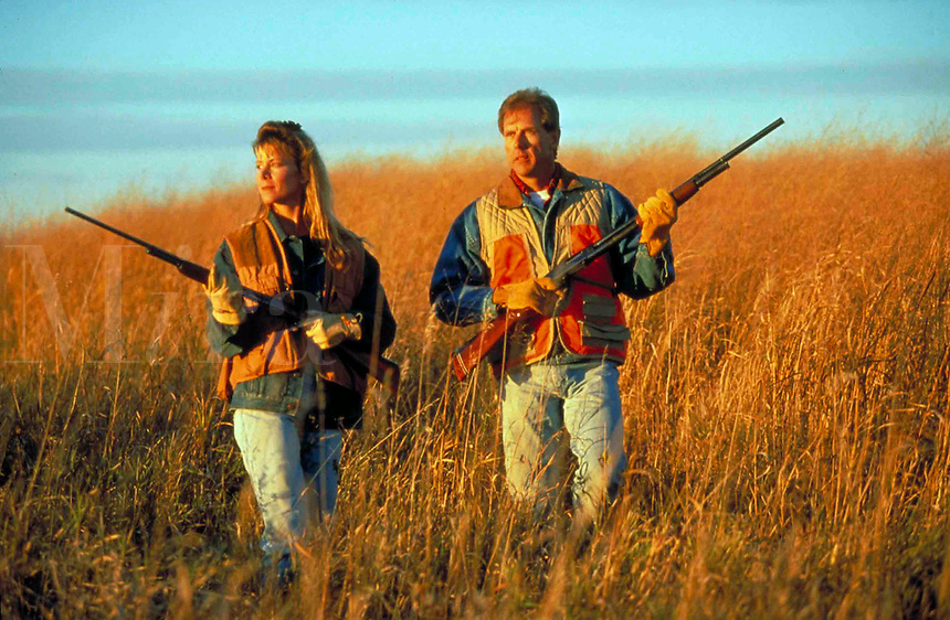 Man and woman bird hunting (pheasant) in Iowa grasslands.