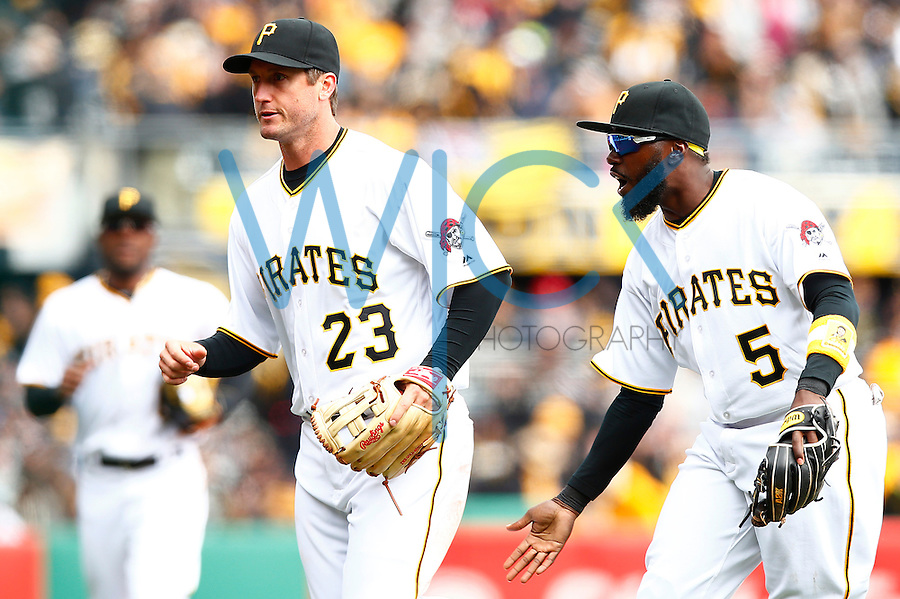 Josh Harrison #5 of the Pittsburgh Pirates congratulates David Freese #23 of the Pittsburgh Pirates after making a play against the St. Louis Cardinals during the Opening Day game at PNC Park in Pittsburgh, Pennsylvania on April 3, 2016. (Photo by Jared Wickerham / DKPS)