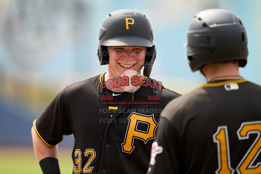 FCL Pirates Black Henry Davis (32) jokes with Dustin Fowler (12) during a pitching change in the top of the third inning during a game against the FCL Rays on August 3, 2021 at Charlotte Sports Park in Port Charlotte, Florida.  Davis was making his professional debut after being selected first overall in the MLB Draft out of Louisville by the Pittsburgh Pirates.  (Mike Janes/Four Seam Images)