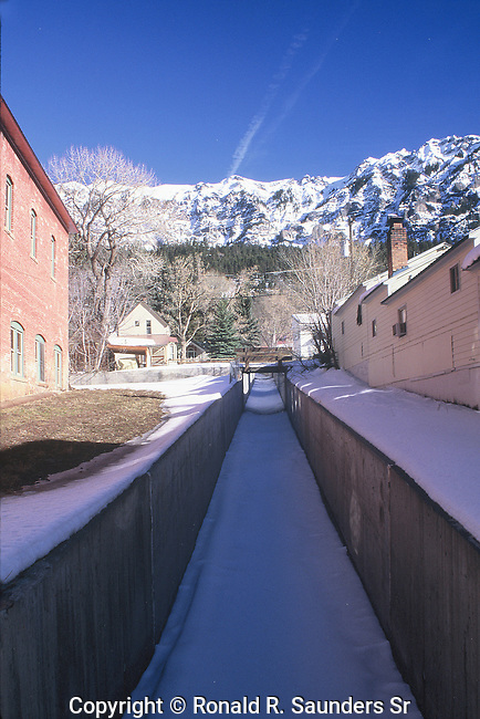 BRIDGE OVER SNOW COVERED STREAM IN COLORADO MOUNTAIN TOWN