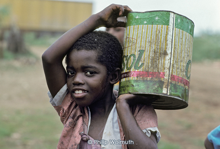 Child of a Haitian migrant cane-cutter carries a can of water from the hand-pumped well which serves the 'batteye' on a sugar plantation in San Pedro de Macoris, Dominican Republic