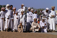 Mudayrib, Oman, Arabian Peninsula, Middle East - Omani men and boys watching a camel race.  Items of clothing include the dishdasha (white robe), kumma (embroidered hat), massar (turban), khanjar (curved dagger).  Several also carry the asa, or khuzran, the traditional Omani walking stick.
