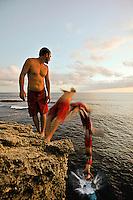 Young man cliff jumping off the bluff at Shipwreck Beach, Poipu, Kauai, Hawaii