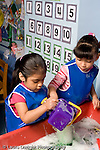 Education Preschool 4-5 year olds water table two girls playing together wearing smocks sudsy water vertical