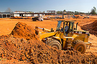 02/22/07:  A Caterpillar tractor scoops a shovelful of bright red/orange clay soil during expansion/construction of a Charlotte-area shopping center. Charlotte, NC, is one of the country's fastest-growing cities. ..By Patrick Schneider- Patrick Schneider Photography.