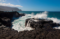 North shore winter waves cascading over black lava rocks at the Queen's Bath area in Princeville, Kauai, with Na Pali cliffs in the background.