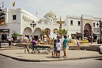 Tunis, Tunisia.  Sidi Mehrez Mosque (1675-92), from Place Bab Souika.  Children Playing in Neighborhood Fountain.  Bab Souika Entrance to the Medina on Right.