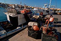 Lampedusa / Italia .Veduta del porto con barche e pescherecci. Nella foto un pescatore impegnato a riparare le reti da pesca..Foto Lvio Senigalliesi