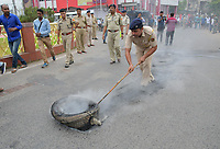 Pictured: A police officer attempts to remove a burning tyre. Re: Activists of the Congress political party clash with police in protest against price rises in oil, gas and other daily commmodities by BJP government in Agartala, in the Tripura area of India. Monday 10 September 2018
