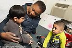 Education preschool 3 year olds sad boy sitting on lap of female teacher, classmate looking on