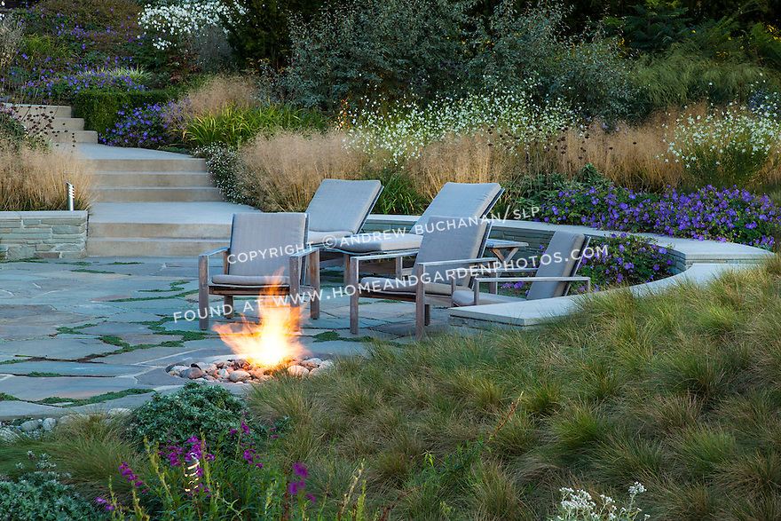 With a lush meadow garden behind, a stacked stone wall curves around a stone patio and firepit.