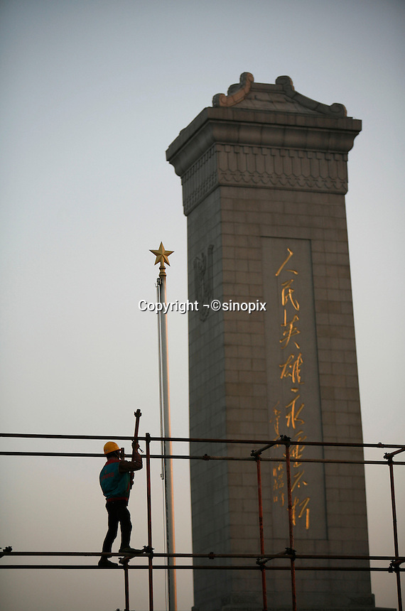 Workers stand on a scaffolding near the Monument to the People's Heros at the Tiananmen Square in Beijing, China..06 Sep 2006