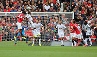 Pictured: Ashley Williams of Swansea (2nd L) heads the ball away from Marouane Fellaini of Manchester United. Saturday 16 August 2014<br />
