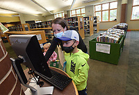 Chritsine Starch (cq) and her son, Lincoln, 8, check the card catalog on Tuesday April 20 2021 in the children's area of the Bentonville Public Library. <br />(NWA Democrat-Gazette/Flip Putthoff)