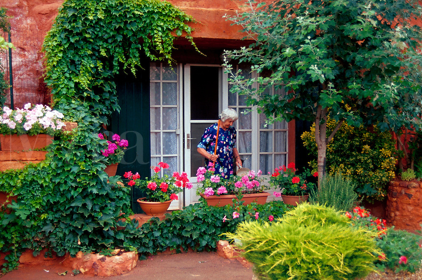 A senior French woman sweeps the beautiful exterior courtyard of her home. Rousillon, France.