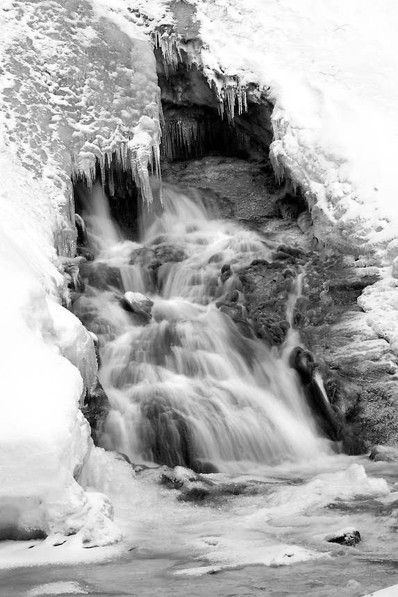A close-up shot of water flowing out of the base of a partially frozen Munising Falls.