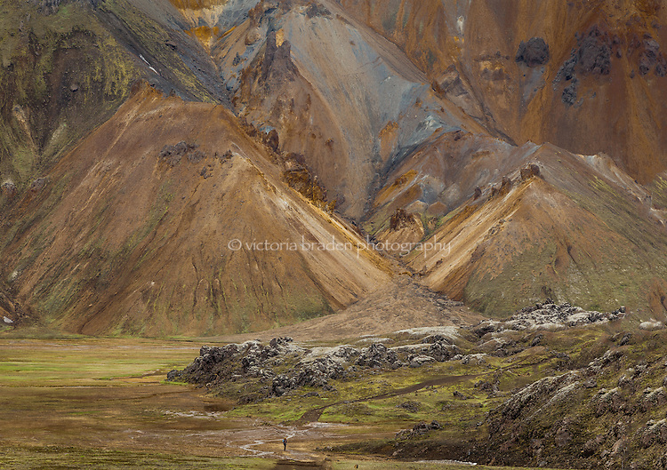 A hiker is dwarfed by the massive hills and colors in the Highlands of Iceland
