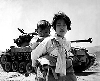 With her brother on her back a war weary Korean girl tiredly trudges by a stalled M-26 tank, at Haengju, Korea.  June 9, 1951.  Maj. R.V. Spencer, UAF. (Navy)<br /> NARA FILE #:  080-G-429691<br /> WAR & CONFLICT BOOK #:  1485