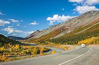"Motorhome travels the Richardson Highway, vibrant fall colors along the Alaska Range mountain ridge named ""Rainbow Mountain"", Interior, Alaska."