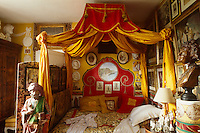 A red and yellow lit a la Polonaise dominates this bedroom which is cluttered with objects, medallions and paintings