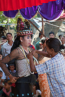 Myanmar, Burma, Bagan.  Nat Pwe, a Ceremony to Thank the Spirits for a Year of Good Fortune.  A villager pins a banknote to the dancer's blouse as an offering.