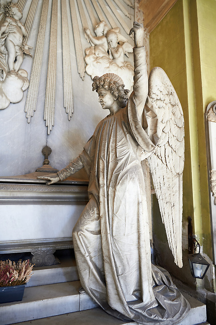 Picture and image of the stone sculpture of an angel standing by a stone sarcophagus. The Croce Tomb sculpted by G Moreno 1889. Section A, no 23, The monumental tombs of the Staglieno Monumental Cemetery, Genoa, Italy