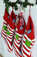 Knitted red and white striped Christmas stockings, each with their own mouse, hang from a cupboard in the kitchen
