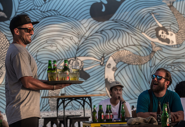 6 DECEMBER, 2019 BALI, INDONESIA: Aiden Mephan from Perth with a tray of happy hour drinks to watch the sunset with friends at Old Man's in Canggu, Bali. There has been a levelling out of Australian tourist numbers to Bali in recent times and tastes are changing regarding what people want from their holiday. Millennials are being targeted by tourism authorities and they want to give them more boutique experiences than just beach and beer. Picture by Graham Crouch/The Australian