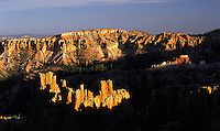 Highly-eroded pinnacles and cliffs in Bryce Canyon, Utah, dramatically lit in low evening light. Bryce Canyon, Utah, US