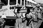 Ciudad Cuauhtémoc, Mexico 1970s. Indigenous native Indian women carry food in baskets on their heads.  They are selling snacks something to eat to the bus passengers at a  bus station rest stop on the  Pan American Highway. 1973