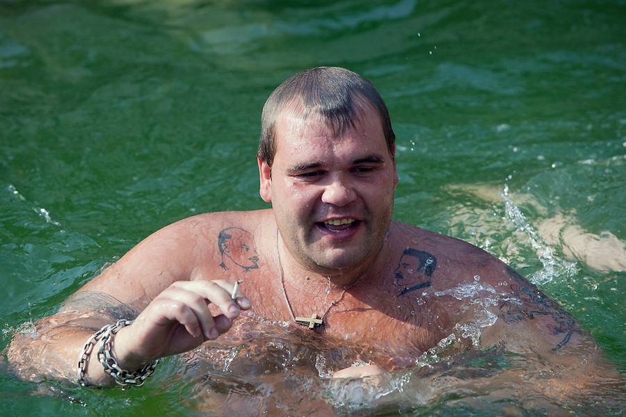 Moscow, Russia, 16/07/2010..A man adorned with a variety of tattoos, including images of Lenin and Stalin, and the words Dum Spiro Spero [As long as I breathe, I hope] cools off in fountains next to the Kremlin and Red Square during a prolonged heatwave that has seen temperatures of over 37C, a record for the city. Such tattoos are common amongst Russian prison inmates, and contain a system of codes denoting the owner's status and history within the country's criminal system.