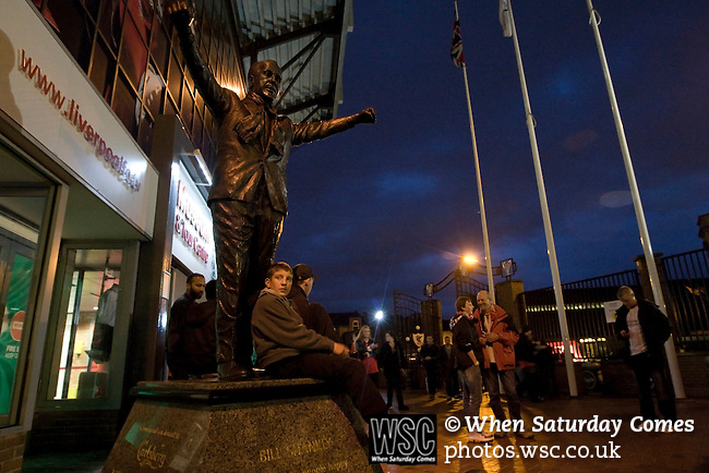 Liverpool 2 Northampton Town 2, 22/09/2010. Anfield, League Cup third round. Liverpool supporters sitting below the statue of former manager Bill Shankly outside Anfield, before their team's Carling Cup third round tie at home to Northampton Town. The visitors from English League 2 defeated Premier League Liverpool on penalty kicks after a 2-2 draw after extra time in one of the biggest shock results in either clubs histories. Photo by Colin McPherson.