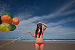 Young woman runs and plays on a beach with balloons that read Happy Birthday