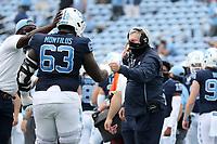 CHAPEL HILL, NC - OCTOBER 10: Head coach Mack Brown of North Carolina fist bumps Ed Montilus #63 during a game between Virginia Tech and North Carolina at Kenan Memorial Stadium on October 10, 2020 in Chapel Hill, North Carolina.