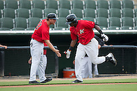 Micker Aldofo (37) of the Kannapolis Intimidators slaps hands with third base coach Cole Armstrong (33) as he rounds the bases after hitting a 3-run home run in the bottom of the 1st inning against the Charleston RiverDogs at Kannapolis Intimidators Stadium on August 3, 2016 in Kannapolis, North Carolina.  The Intimidators defeated the RiverDogs 8-4.  (Brian Westerholt/Four Seam Images)