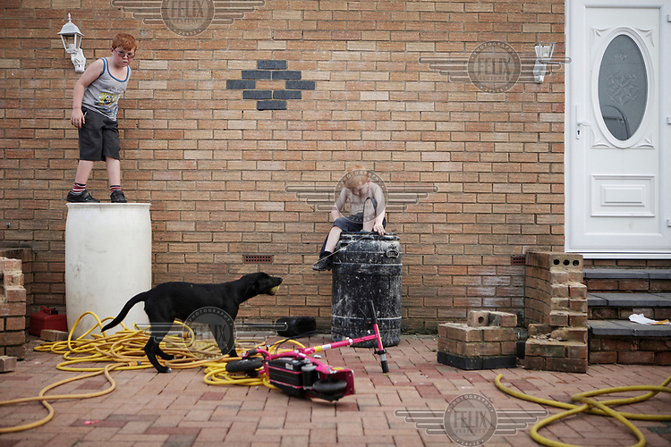 Irish Traveller Barbara Sheridan's two youngest sons Richard (7) and Dennis (5, left), play in their aunt's yard.
