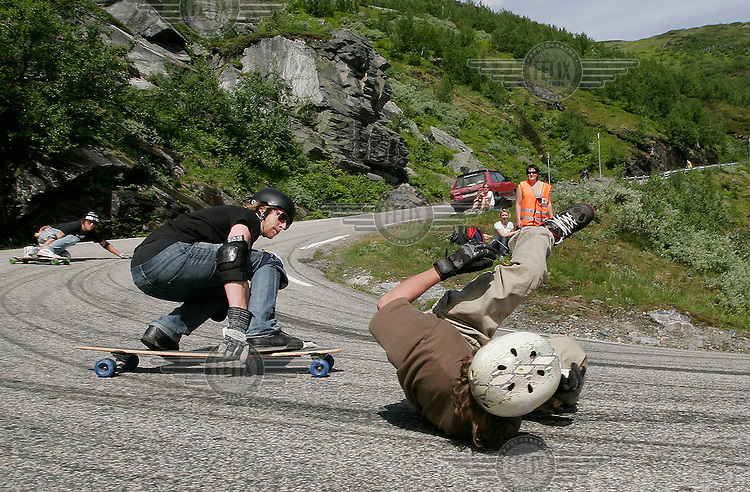 A rider wipes out and almost gets hit by another competitor. The first ever Norwegian Longboarding Championship was held during the Extreme Sport Week, an annual event that draws adrenalin junkies to the small Norwegian mountain town of Voss. © Fredrik Naumann