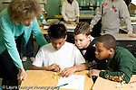 Education Elementary school Grade 5 class with female science specialist teacher making models from toothpicks and mini marshmallows three male students working together horizontal