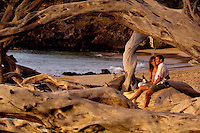 Couple watching sunset under drftwood arch on secluded beach with bottle of wine, Big Island of Hawaii