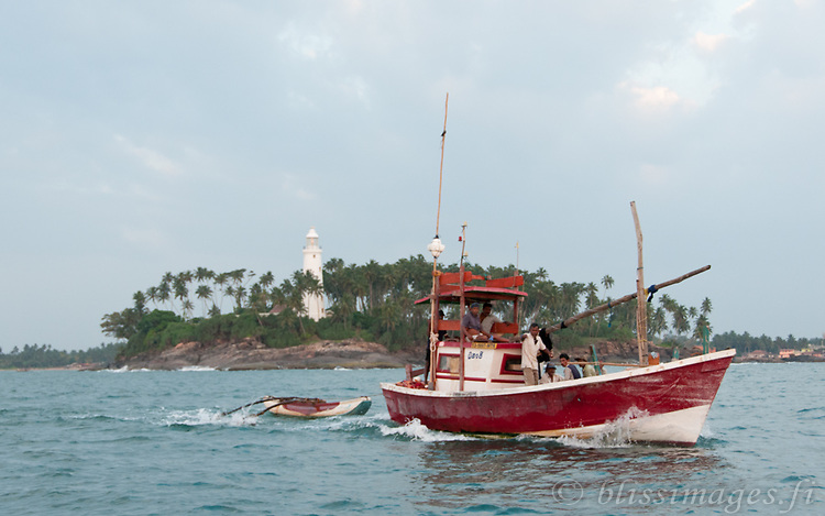 Fishing boat passes Barberyn (Beruwala) Lighthouse as it heads out to sea after sundown for night-time work -Sri Lanka