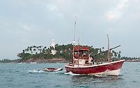 Fishing boat passes Barberyn (Beruwala) Lighthouse as it heads out to sea after sundown for night-time work -Sri Lanka