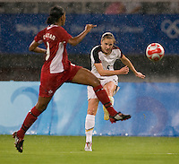 USWNT midfielder (5) Lindsay Tarpley crosses the ball past Canadian defender (9) Candace Chapman while playing at Shanghai Stadium.  The US defeated Canada, 2-1, in extra time and advanced to the semifinals during the 2008 Beijing Olympics in Shanghai, China.