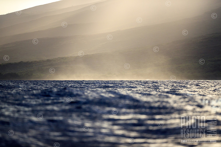 Ocean mist rises from the shores to the hills of Lana'i, as seen from a sunset whale watching cruise in the waters between Lana'i and Maui.