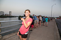 Fit attractive young, Austin woman hangs out on the Congress Ave. Bat Bridge while waiting for the bats to take flight in downtown Austin, Texas.