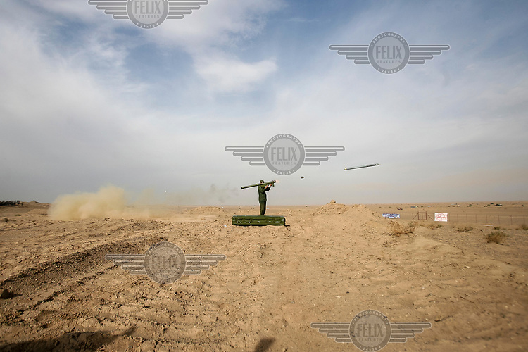 A member of Iran's elite Revolutionary Guard fires a shoulder launched rocket during training manoeuvres in a central desert.